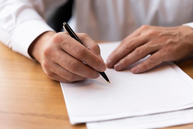 Homme d'affaires écrit sur du papier vierge Photo gratuit