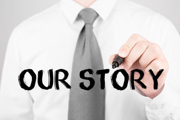 Homme d'affaires écrit le mot notre histoire avec marqueur, concept d'entreprise Photo Premium