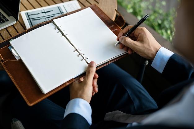 Homme D'affaires écrit Une Note Sur Un Cahier Photo Premium