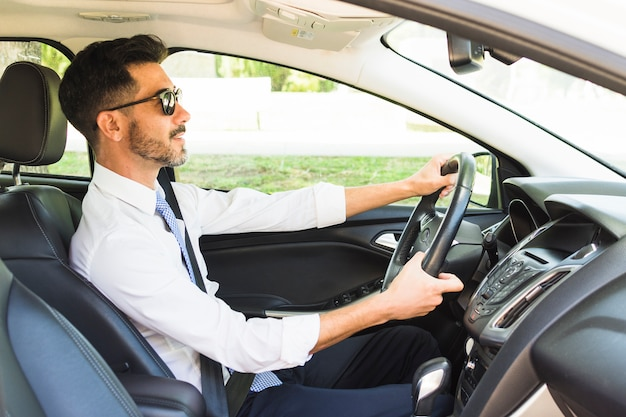 Homme d'affaires élégant, lunettes de soleil au volant de la voiture Photo gratuit