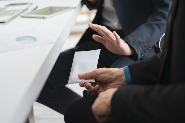 Un homme d'affaires essayant de donner un pot-de-vin à un autre homme d'affaires. Photo Premium