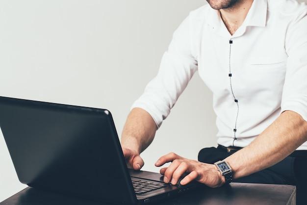 Un homme d'affaires est assis à la table et travaille derrière un ordinateur portable au bureau. un homme tape un message sur un ordinateur portable Photo Premium