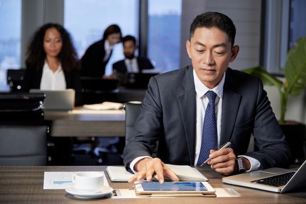 Homme D'affaires Ethnique Concentré à L'aide De Tablette Photo gratuit