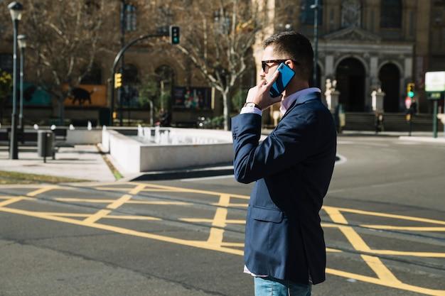 Homme d'affaires faisant un appel téléphonique en milieu urbain Photo gratuit