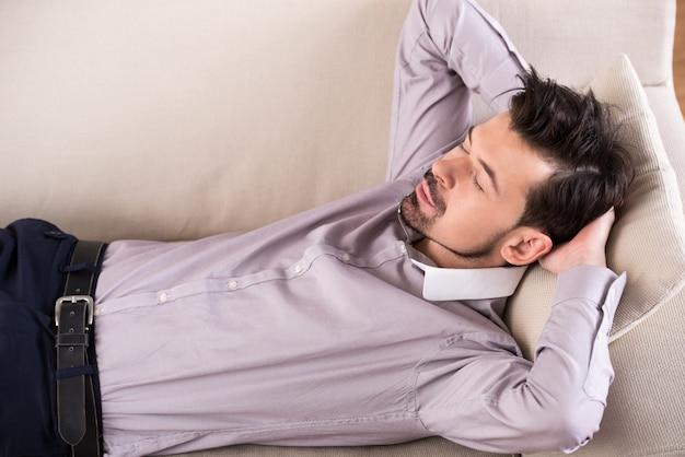 Homme d'affaires fatigué dort sur le canapé au bureau. Photo Premium