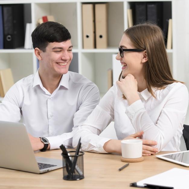 Homme d'affaires et femme d'affaires assis ensemble sur le lieu de travail en regardant les uns les autres Photo gratuit