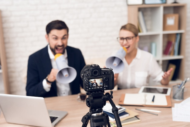 Homme d'affaires et femme d'affaires criant en mégaphones. Photo Premium