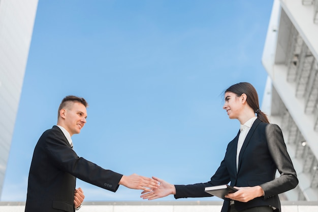 Homme d'affaires et femme d'affaires se serrant la main Photo gratuit