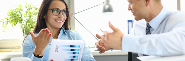 Homme D'affaires Et Femme D'affaires Sont Assis à Table Au Bureau Ayant Un Dialogue. Photo Premium