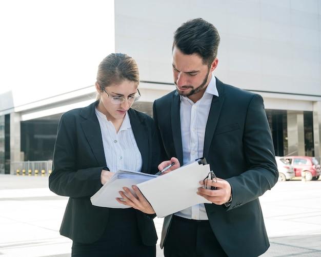 Homme d'affaires et femme d'affaires vérifiant les documents à l'extérieur Photo gratuit