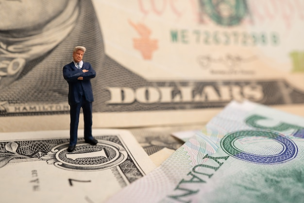Homme d'affaires figure sur un billet de banque en dollars américains et yuan Photo Premium
