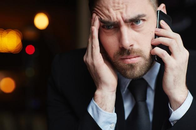 Homme d'affaires frustré parlant au téléphone Photo gratuit