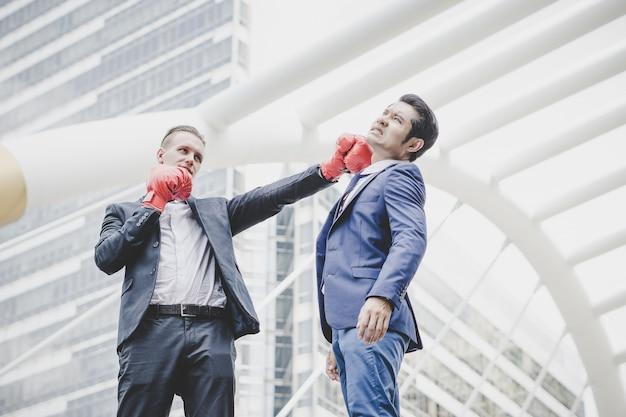Homme d'affaires avec des gants de boxe rouges prêts à se battre contre son collègue. Photo gratuit