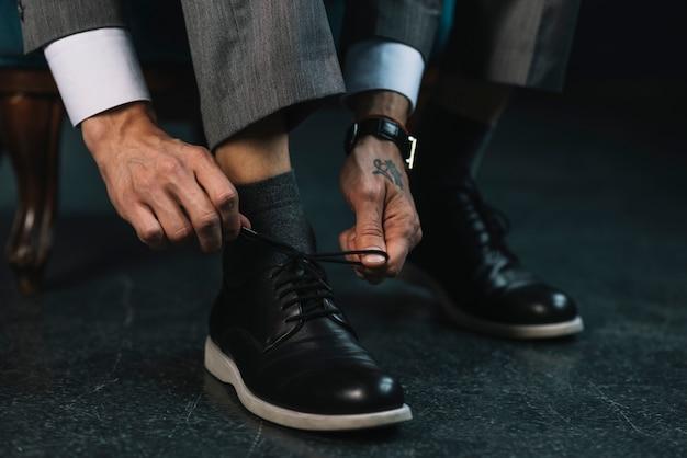 Homme affaires, habillage, à, classique, élégant, chaussures, attacher, lacet Photo gratuit