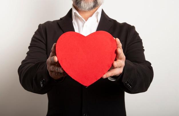 Homme D'affaires Habillé En Costume Tenant Un Coeur Rouge Sur Fond Blanc. La Saint Valentin Avec Un Moment Doux Et Romantique. Photo Premium
