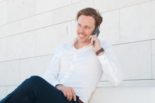 Homme d'affaires heureux appeler sur un smartphone sur un banc à l'extérieur Photo gratuit