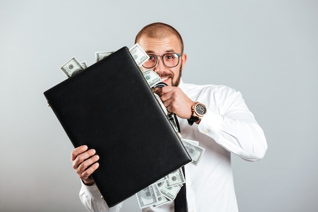 Homme D'affaires Heureux Dans Des Verres Et Une Chemise Tenant Un Diplomate Plein D'argent Comptant, Isolé Sur Mur Gris Photo Premium
