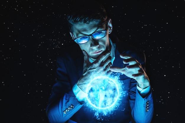 Homme d'affaires homme tenant la main sur une sphère de plasma rougeoyante bleue. prédiction magique et prospective en affaires et en finance Photo Premium