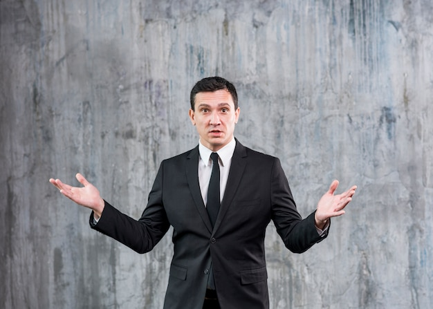Homme d'affaires incompris debout avec les mains levées Photo gratuit