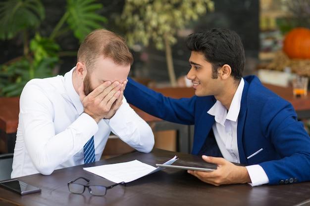Homme d'affaires indien soutenant un collègue et lui caressant le dos Photo gratuit
