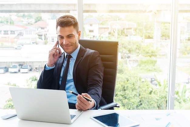 Homme d'affaires intelligent utilisant mobile et ordinateur portable au bureau. Photo Premium