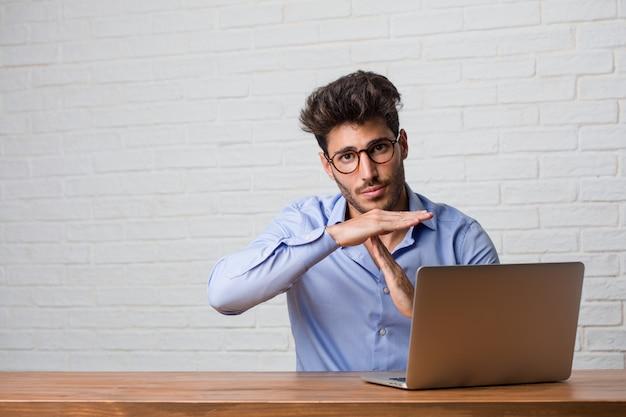Homme d'affaires jeune assis et travaillant sur un ordinateur portable fatigué et ennuyé, faisant un geste de délai d'attente, doit arrêter en raison du stress au travail, notion de temps Photo Premium