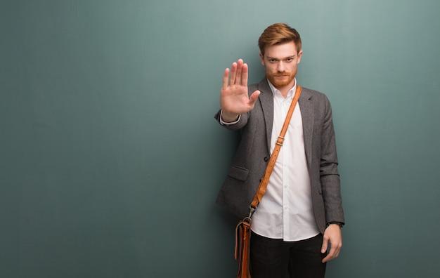 Homme d'affaires jeune rousse mettant la main devant Photo Premium