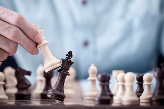 Homme d'affaires joue avec le jeu d'échecs dans le succès de la compétition Photo Premium