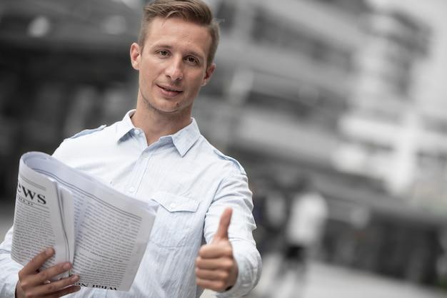 Homme d'affaires avec journal abandonnant le pouce pour de bonnes nouvelles. Photo Premium