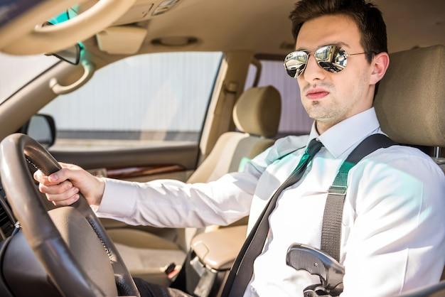 Homme D'affaires En Lunettes De Soleil Avec Arme à Feu Dans Sa Voiture De Luxe. Photo Premium
