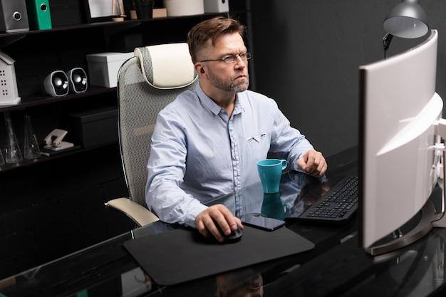 Homme d'affaires avec des lunettes travaillant dans le bureau à la table d'ordinateur et de boire du café Photo Premium