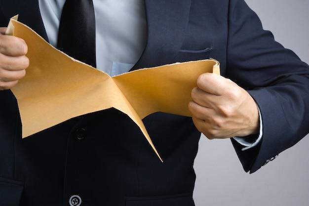 Homme d'affaires main déchirant le document enveloppe auto-scellant brun dans la colère Photo Premium