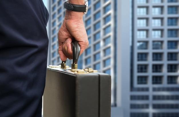 L'homme d'affaires de la main porte un bref sac à main sur le chemin du bureau. Photo gratuit
