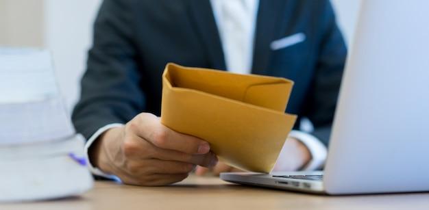 Homme d'affaires main tenant et envoyer une enveloppe secrète tan Photo Premium