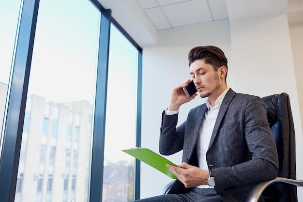 Homme D'affaires Avec Les Mains De Documents De Parler Sur Une Cellule Dans Moderne Photo Premium
