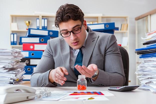 Homme d'affaires malade avec des médicaments au bureau Photo Premium