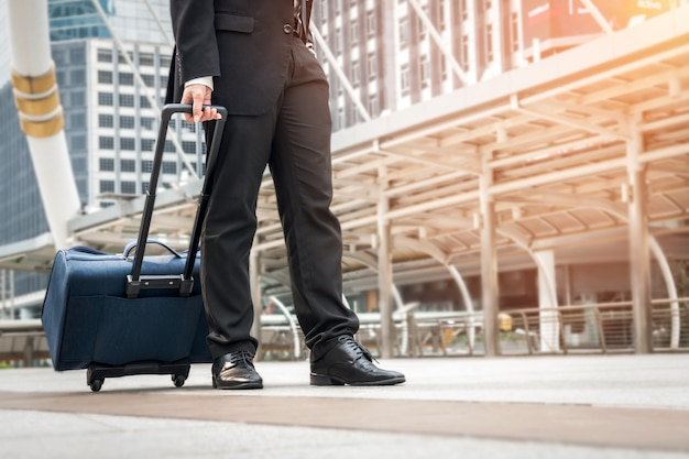 Homme d'affaires marchant sur le chemin de l'aéroport avec des bagages Photo Premium