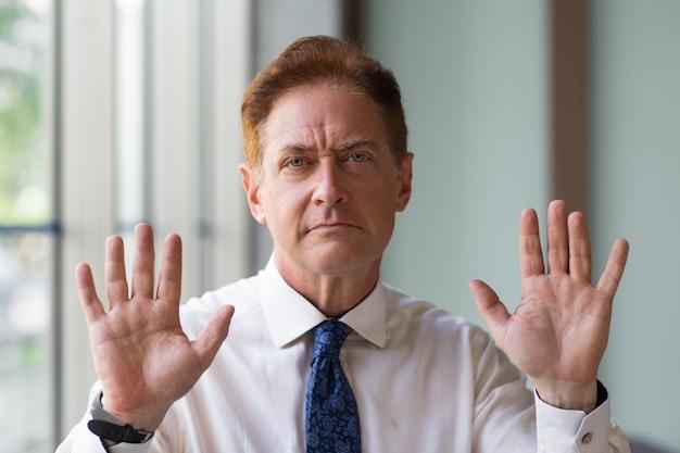 Un Homme D'affaires Mature Mécontent Montrant Un Geste D'arrêt Photo gratuit