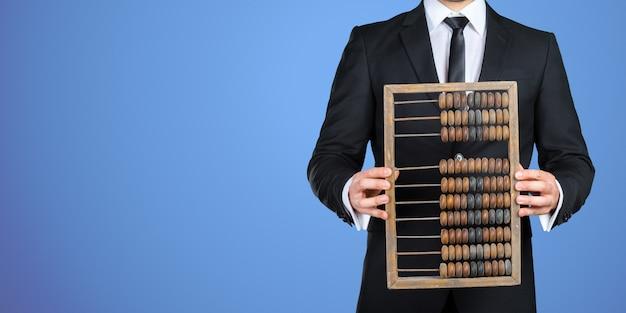 Homme d'affaires méconnaissable vous montrant un boulier vintage. concept commercial Photo Premium