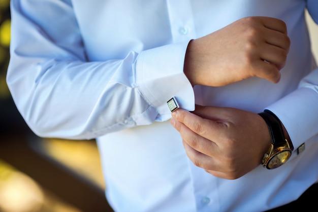 Homme d'affaires met des boutons de manchette. marié se prépare le matin avant la cérémonie de mariage Photo Premium