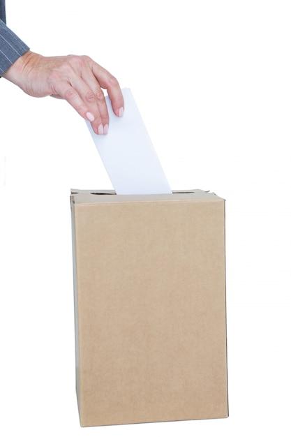 Homme d'affaires mettant le bulletin de vote dans la boîte de vote Photo Premium