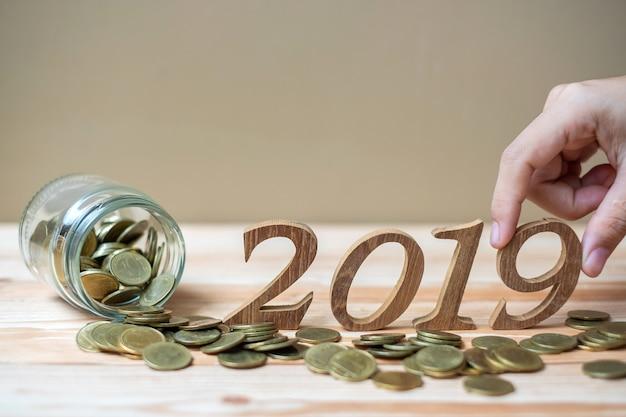 Homme d'affaires mettant le numéro «2019» en bois avec une pile de pièces d'or Photo Premium