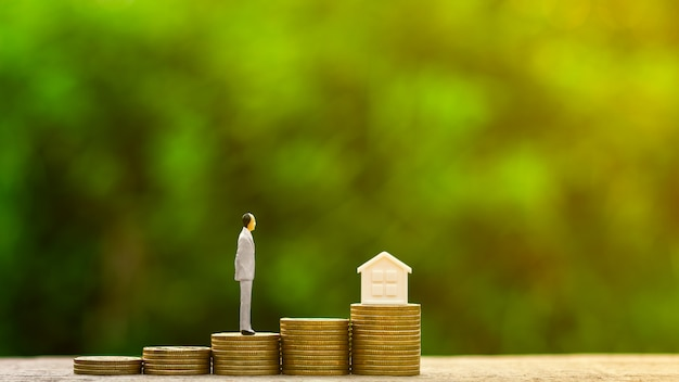Homme d'affaires miniature, debout sur une pile de pièces d'or Photo Premium