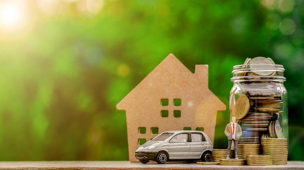 Homme d'affaires miniature se tenant debout sur une pièce d'or et un modèle de voiture Photo Premium