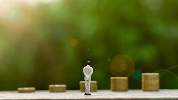 Homme d'affaires miniature se tenant debout pour voir l'avenir des pièces d'or Photo Premium