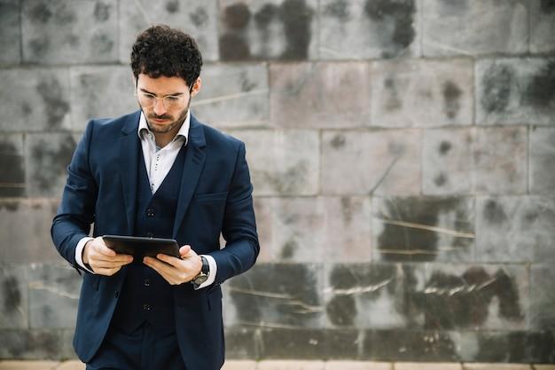Homme d'affaires moderne à l'aide d'une tablette devant le mur Photo gratuit