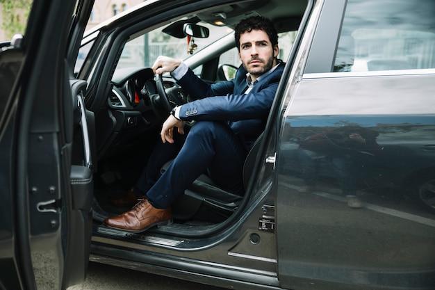 Homme d'affaires moderne assis dans la voiture Photo gratuit