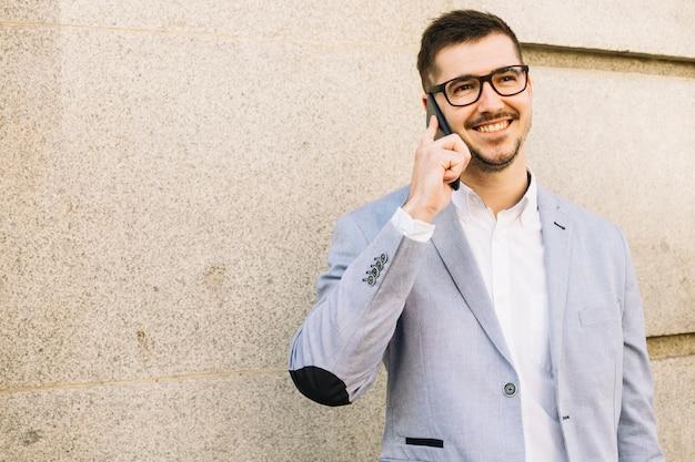 Homme d'affaires moderne faisant un appel téléphonique à l'extérieur Photo gratuit