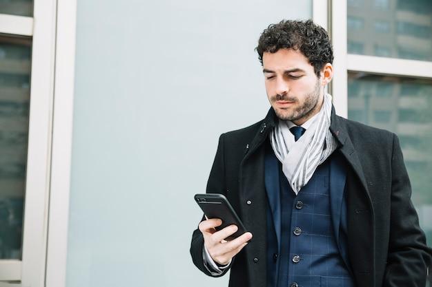 Homme d'affaires moderne utilisant un appareil à l'extérieur Photo gratuit