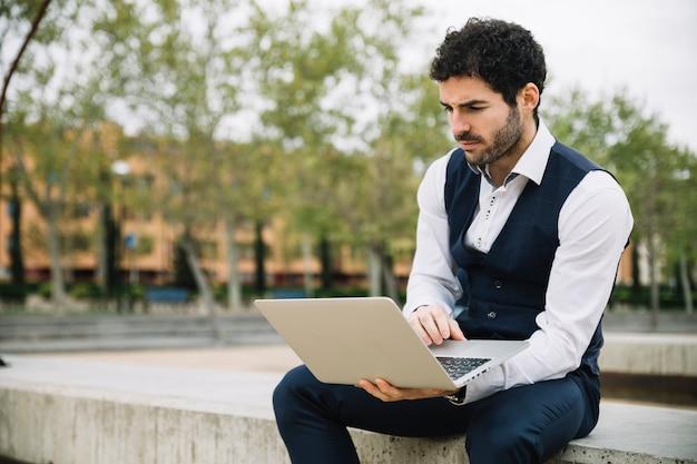 Homme d'affaires moderne utilisant un ordinateur portable à l'extérieur Photo gratuit